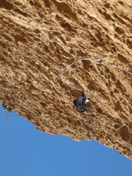 Linus zekert mij doorheen de laatste 6b+ lengte, door de vallijn van het touw wordt duidelijk hoe hallucinant de overhang is! In de verte zie je Jan en Jasper © Denis