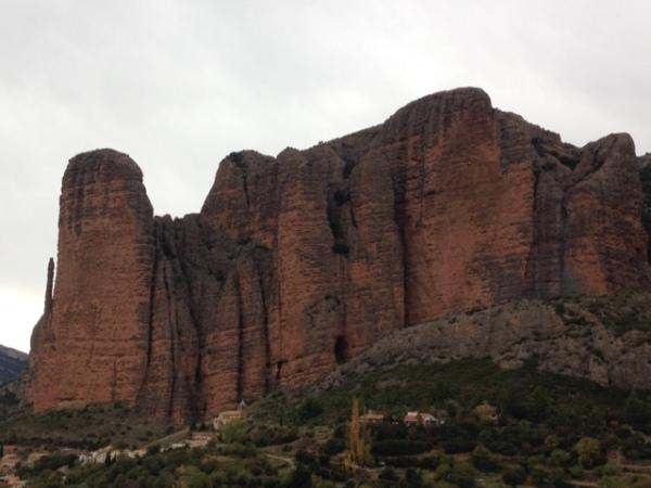 Mallos de Riglos, met het dorpje links onderaan in beeld, en de twee meest prominente wanden (links de Pison-toren en rechts de overhangende Visera-wand) © Denis